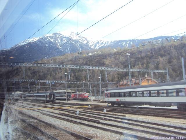 Trenes cerca de la frontera Italia-Suiza con los Alpes de fondo